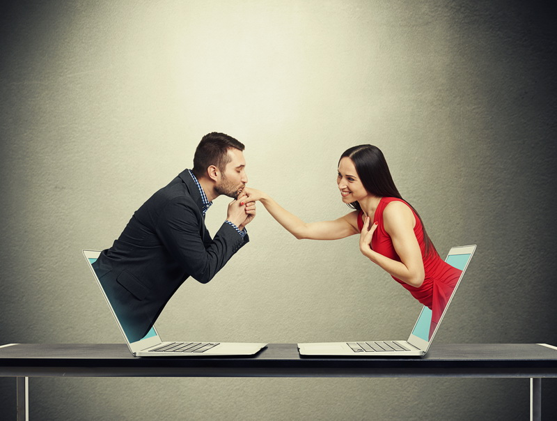 concept of love in social network. young man got out of the computer and kissing hand of beautiful young woman who got out of another computer over dark grey background